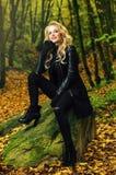 女孩室外坐在秋天风景的一块石头 免版税图库摄影