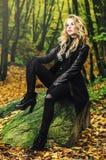 女孩室外坐在秋天风景的一块石头 免版税库存图片