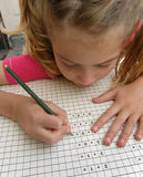 女孩家庭作业writening算术的学童 免版税库存照片
