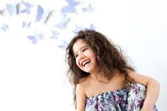 女孩对用蝴蝶装饰的墙壁 库存照片