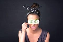女孩对负纸与绿色美元的符号 库存照片