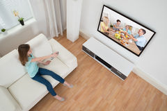 女孩对负遥控在电视前面 库存图片