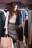 女孩寻找一件理想的礼服 免版税库存图片