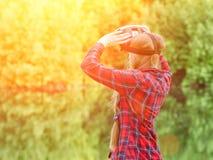 女孩射击虚拟现实玻璃,日落本质上,从后面的看法 免版税库存图片