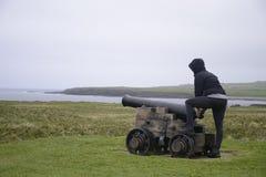 女孩射击大炮奥克尼海岸线峭壁风景 库存照片