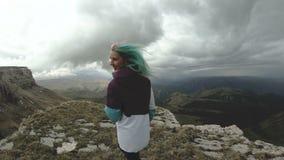 女孩少妇跳舞在有的高原的峭壁边缘乐趣自然山花美丽有吸引力 股票录像