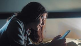 女孩少年和智能手机 小青少年的敞篷女孩在社会媒介信使夜写一种消息聊天的生活方式 股票录像