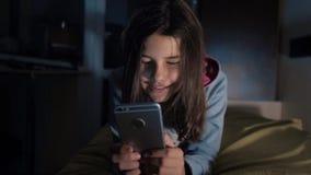 女孩少年和智能手机 聊天小青少年的敞篷的女孩在社会媒介信使夜晚上写一则消息 股票视频