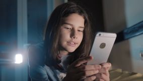 女孩少年和智能手机 聊天小青少年的敞篷的女孩在社会媒介信使夜晚上写一则消息 影视素材