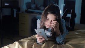 女孩少年和智能手机 聊天小青少年的敞篷的女孩在社会媒介信使夜晚上写一则消息 股票录像