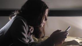 女孩少年和生活方式智能手机 聊天小青少年的敞篷的女孩在社会媒介信使夜写一则消息 股票录像