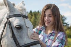 女孩少年和白马在一个公园在一个夏天 库存照片