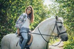 女孩少年和白马在一个公园在一个夏天 免版税库存照片