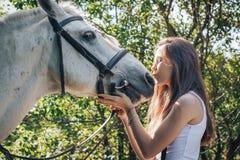 女孩少年和白马在一个公园在一个夏天 库存图片