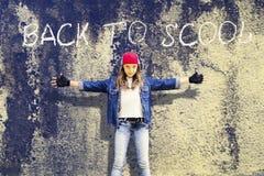 女孩少年用广泛单独的手 牛仔布衣物 棒球帽 以老混凝土墙为背景 登记 免版税图库摄影