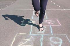 女孩少年跳演奏在街道的跳房子 特写镜头腿 图库摄影