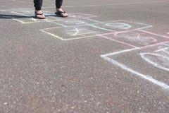 女孩少年跳演奏在街道的跳房子 特写镜头腿 免版税库存照片