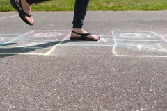 女孩少年跳演奏在街道的跳房子 特写镜头腿 免版税库存图片