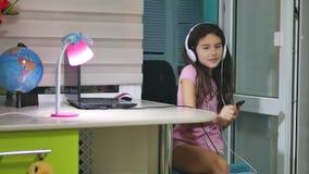 女孩少年跳舞和唱歌在音乐耳机 女小学生听到音乐在网上和户内舞蹈并且唱歌 影视素材