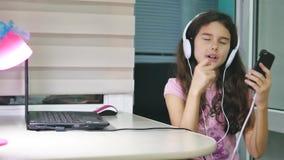 女孩少年跳舞和唱歌在音乐耳机 女小学生在网上听到音乐并且跳舞并且唱歌户内 股票视频