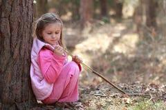 女孩少许坐的木头 免版税库存图片