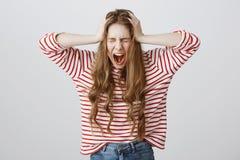 女孩尖叫从精神不稳定 呼喊和握在头的沮丧的厌烦的少妇画象手 库存图片