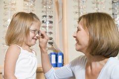 女孩尝试妇女年轻人的玻璃验光师 库存照片