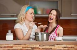 女孩尝试汤在厨房里 免版税库存图片