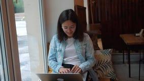 女孩工作在一个窗口前面的一台膝上型计算机在咖啡馆 年轻俏丽的女商人在一个黑暗的咖啡馆坐并且努力工作在 股票录像