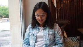 女孩工作在一个窗口前面的一台膝上型计算机在咖啡馆 年轻俏丽的女商人在一个黑暗的咖啡馆坐并且努力工作在 股票视频