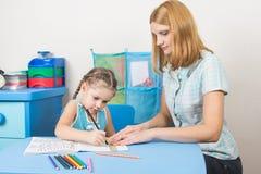 女孩帮助一个五年女孩画与统治者的一条直线 库存图片