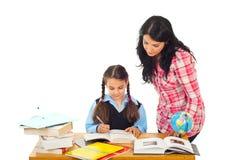 女孩帮助的家庭作业妈妈 免版税库存照片
