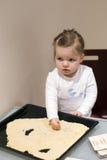 女孩帮助的母亲在厨房里 免版税库存图片