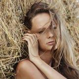 女孩干草堆下纵向 免版税库存照片