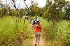 女孩平衡在头的水,当远足与旅游小组Thro时 免版税库存照片