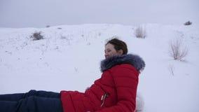 女孩幻灯片在雪的冬天从在雪撬和一支可膨胀的雪管的高小山 青少年的女孩充当冬天公园  股票视频