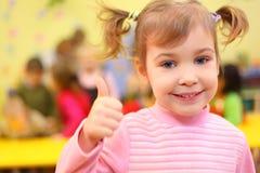 女孩幼稚园一点好显示微笑 免版税库存图片