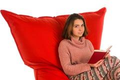 女孩开会和读书在红场的一本书塑造了装豆子小布袋sof 库存图片