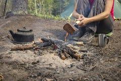 女孩开会,当野营在火加热了和饮料热的茶附近时 图库摄影