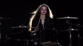 女孩开始演奏精力充沛的音乐的鼓手,她微笑 黑色背景 慢的行动 股票视频
