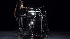 女孩开始演奏精力充沛的音乐的鼓手,她微笑 黑色背景 慢的行动 影视素材