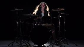 女孩开始演奏精力充沛的音乐的鼓手,她微笑 黑色背景 慢的行动 股票录像