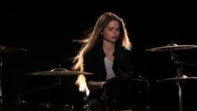 女孩开始演奏精力充沛的音乐的鼓手,她微笑 黑色背景 股票视频