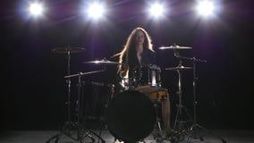 女孩开始演奏精力充沛的音乐的鼓手,她微笑 黑色背景 影视素材