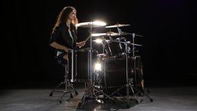 女孩开始演奏精力充沛的音乐的鼓手,她微笑 黑色背景 股票录像