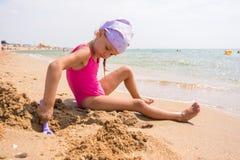 女孩开掘在沙子的一个孔在海滩 库存图片