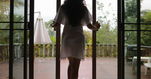 女孩开放阳台出去对大阳台后面背面图,热带森林的早晨视图 影视素材