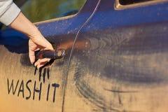 女孩开放非常泥泞的汽车弄脏她手 Autowash概念、词组洗涤它和copyspace 免版税图库摄影