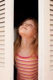女孩开窗口 免版税库存照片