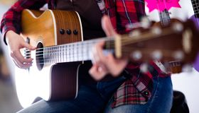 女孩弹声学吉他 在吉他身体的焦点  库存图片